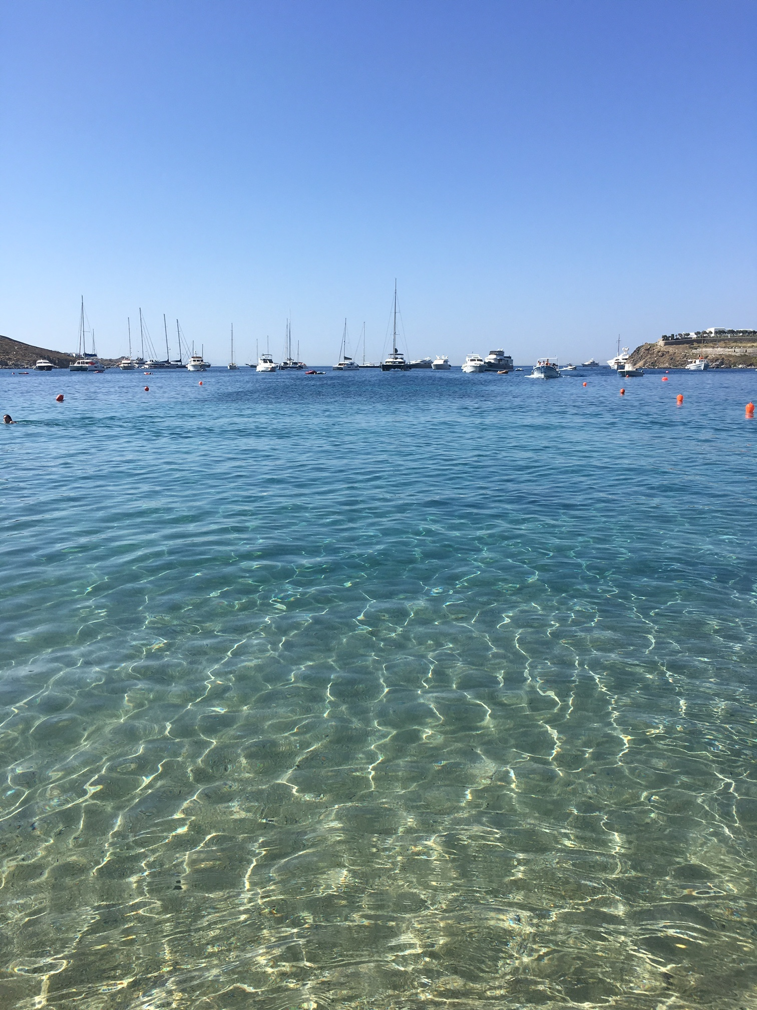 beach, crystal water, blue sky and boats